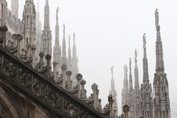 the roof of the Milan's Duomo or cathedral under a heavy day of fog.  the pinnacles, details and sculptures of this magnificent building located in Italy.
