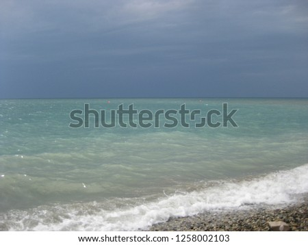 The sea on a cloudy day in all shades of blue and turquoise. White foam on the beach, light gray in shallow water and then to the horizon turquoise. The sky on the horizon violet, and higher dark  Сток-фото ©