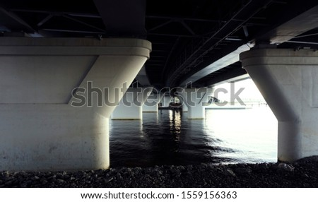 The structure of the bridge, architectural columns, illuminated by bright light on a cloudy day, creating a contrasting shadow on the waters of the Gulf of Finland under the highway #1559156363