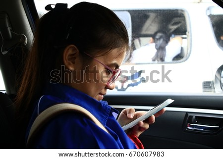 The students wear glasses to play phone, morning on the street on a signal light. Rain in the morning traffic on road congestion. #670607983