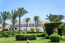 The territory of the hotel. The hotel complex in Egypt is ready for the opening of the tourist season. Well-groomed green area near the house. Landscaping.