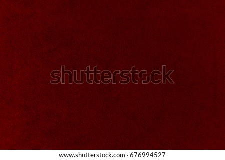 The texture of the  burgundy velvet. The background of burgundy cloth. Background of  burgundy velvet.