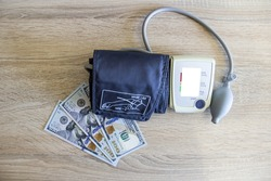 The tonometer lies on the money on the table. Money US dollars lie on the table next to the tonometer.