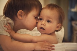 The two brothers friendly and lovingly kiss each other.