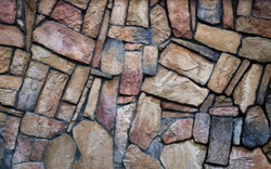 The wall is made of multi-colored natural stone, the masonry is stone on cement. Concept - stone wallpaper, background and decor