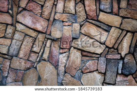 The wall is made of multi-colored natural stone, the masonry is stone on cement. Concept - stone wallpaper, background and decor ストックフォト ©