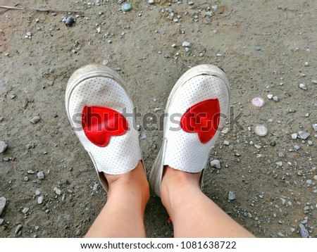 The woman's feet are resting. The feet are in white shoes, decorated with red hearts laid on the ground. #1081638722