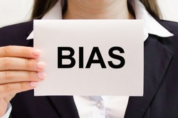 The word bias is written in a notebook held by a businesswoman. judgment bias concept. High quality photo