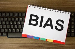 The word bias is written on a white piece of paper that is on the keyboard. the concept of bias bias of personal opinion,. High quality photo