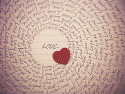 the word love written on a lined piece of school paper in ink with a vignette and a circle of love (focus love) and a tiny red heart toned with a retro vintage instagram filter effect app or action