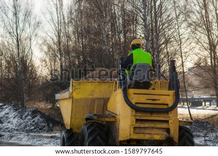 The worker transports the soil. Heavy duty machinery construction equipment.