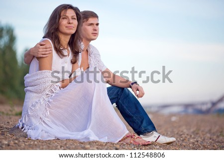 The young pair sits on a beach