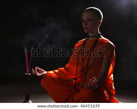 The young woman in orange robers in meditation