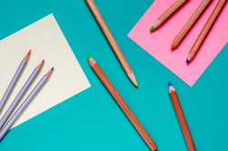 Three groups of colored pencils randomly on the table. Nine multi-colored pencils divided into three groups. Sort by distinguishing features. View from above. Selective focus. Close-up.