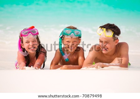 Three happy children on beach with colorful face masks and snorkels, sea in background.