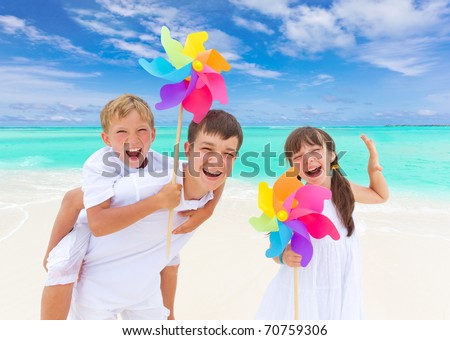 Three happy children with colorful windmills on tropical beach, blue sky and cloudscape background.
