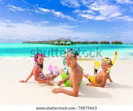 Three happy kids on the beach with snorkel masks.