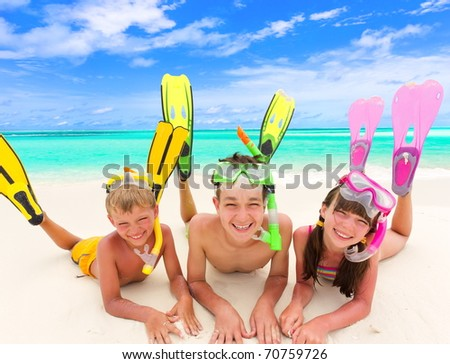 Three happy young children with colorful snorkels and flippers on sandy tropical beach, sea and cloudscape background.