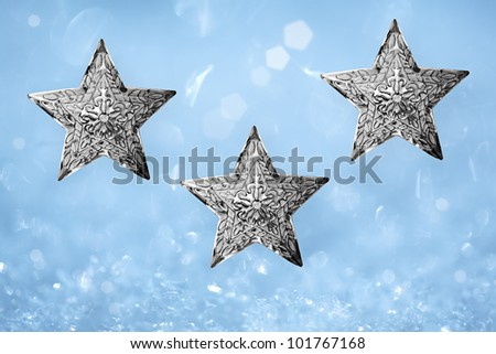 Three Metal Silver Star Christmas Ornaments Over Turquoise Aqua Blue and White Snow Background