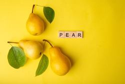 Three pears with green leaves on a yellow background. Nearby there is an inscription in wooden letters