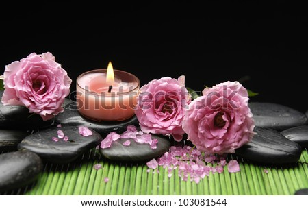 three rose and zen stones with herbal salt with candle in green mat