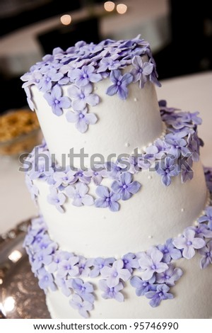 3 tiered wedding cake with purple flowers
