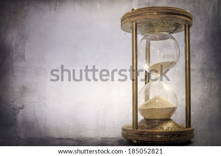 time concept with hourglass lying toned in warm black and white, retro style