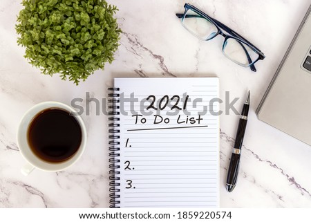 2021 To do list text on note pad with smart phone, laptop, coffee, eyeglasses and pen. Foto d'archivio ©