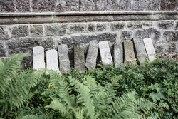 Tombstones with numbers near the cemetery wall