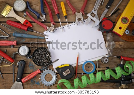 Tools on a timber floor, the top view. Tools are spread out round a notebook for records. A place for your text.