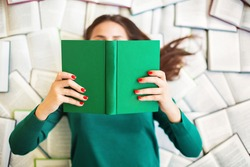 Top view of anonymous female student lying on books and reading during exam preparation