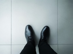 Top view of the black leather shoes on the cement floor. Black men's shoes with long pants on the floor.