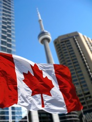 TORONTO, CANADA - Canadian flag is waving front of Toronto CN Tower