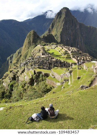 2 tourists looking at the mysterious city of Machu Picchu, Peru