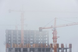 Tower cranes in the early morning fog. Unfinished high-rise buildings. Housing construction, real estate business. Nobody, foggy day.
