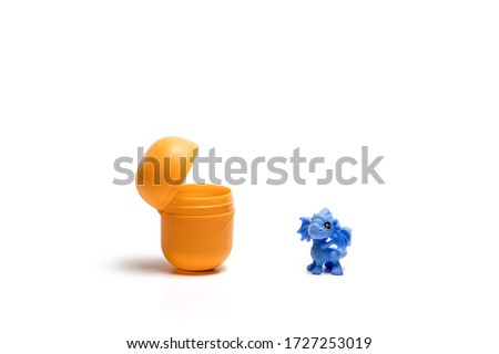 Toy blue dragon from Kinder next to an open yellow egg on a white background Stock foto ©