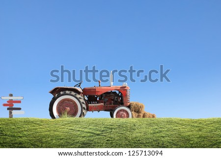 tractor collecting haystack in the field at nice blue