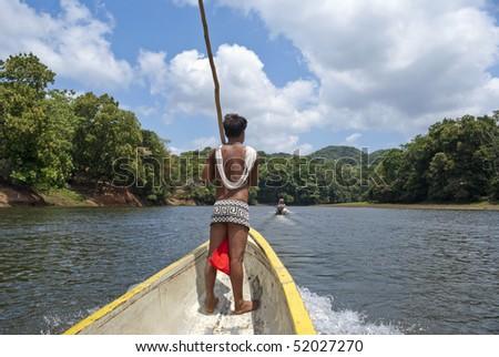 Traditional Embera Indian on long boat at Gambia, Panama.