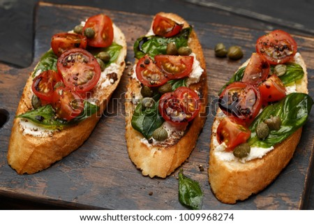Traditional italian bruschetta with cherry tomatoes, cream cheese, basil leaves, capers and  balsamic vinegar on wooden cutting board. Close up view Stock fotó ©