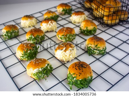 Traditional Turkish pastry, pogaca with cheese filling with dill. Turkish name is 'Sakalli, Sacakli pogaca'. Ingredients are dill and cheese. Stok fotoğraf ©