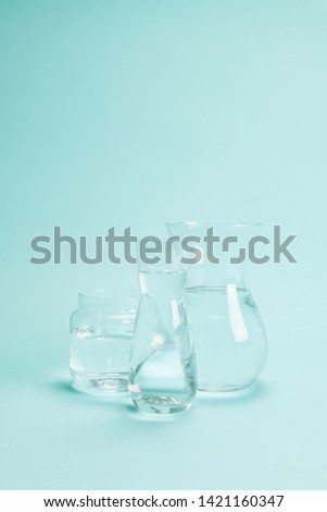 3 transparent glass vases filled with clear water on a turquoise background. Play of light and transparency. Minimal still life color photography #1421160347