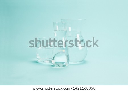 3 transparent glass vases filled with clear water on a turquoise background. Play of light and transparency. Minimal still life color photography #1421160350