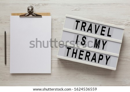 'Travel is my therapy' words on a lightbox, clipboard with blank sheet of paper on a white wooden background, top view. Overhead, from above, flat lay.