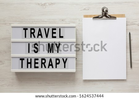 'Travel is my therapy' words on a lightbox, clipboard with blank sheet of paper on a white wooden surface, top view. Overhead, from above, flat lay.