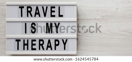 'Travel is my therapy' words on a lightbox on a white wooden surface, top view. Overhead, from above, flat lay. Space for text.