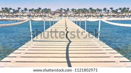 Travel. Pier on the sea. Pier leading to the shore with palm trees.                 #1121802971