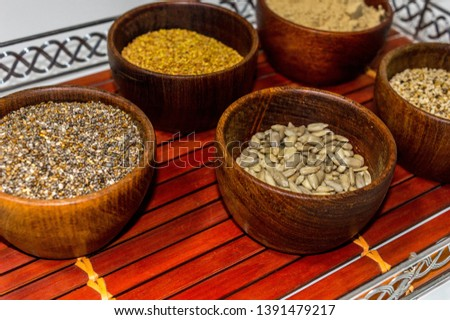 Tray with containers of chia seeds, alfalfa seeds, sunflower seeds, sesame seeds and finally Peruvian maca powder.