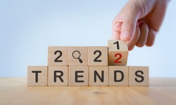 2022 trend concept. Hand flip wooden cube change year 2021 to 2022. Beautiful white background, copy space. Used for banner in trend concept in new year for monitoring new business opportunities.