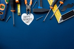 Trendy blue background with tools, black mustache and heart with the inscription: