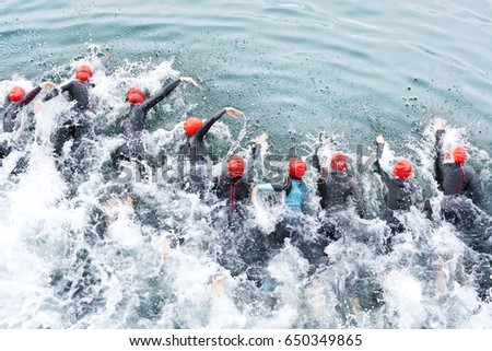 triathlon competitors in swim , triathletes in action and motion